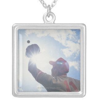 Baseball player catching ball with sun in his silver plated necklace