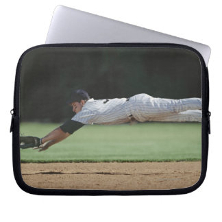 Baseball player in mid-air catching ball. computer sleeve