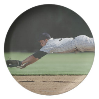 Baseball player in mid-air catching ball. plates
