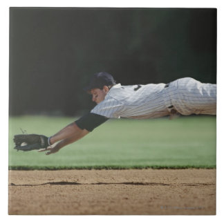 Baseball player in mid-air catching ball. tile