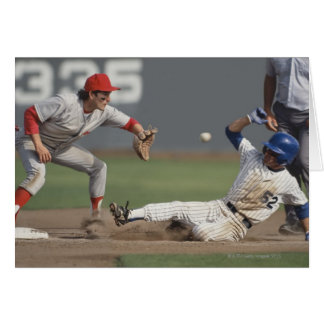 Baseball player sliding into third base with card