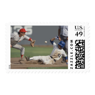 Baseball player sliding into third base with postage