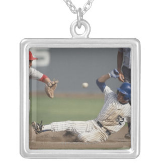 Baseball player sliding into third base with silver plated necklace