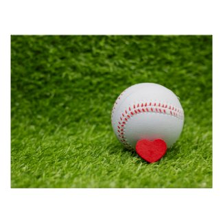 Baseball with red heart are on green grass poster