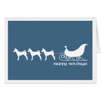 Basenjis que tira del trineo de Santa Felicitación
