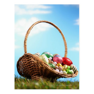 Basket filled with Easter eggs on grass, ground Postcard