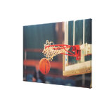 Basketball dropping through hoop stretched canvas prints