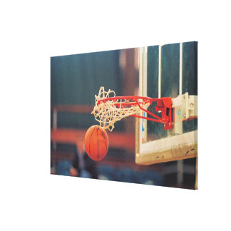 Basketball dropping through hoop canvas print