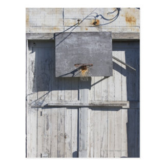 Basketball net on rustic building postcard