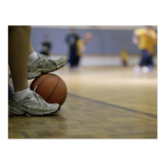 Basketball player holding ball with feet post card