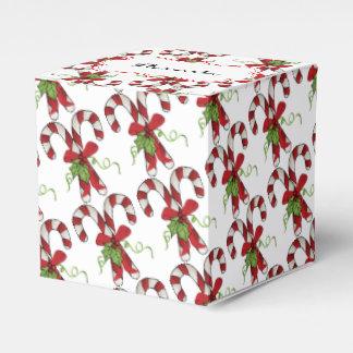 Bastones de caramelo de la raya con acebo y el cajas para detalles de boda