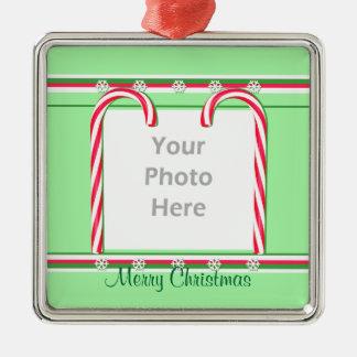 Bastones de caramelo del navidad en el verde adorno cuadrado plateado