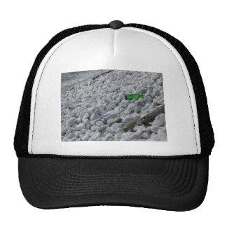 Basura en la playa. Detalle de una botella verde Gorras De Camionero