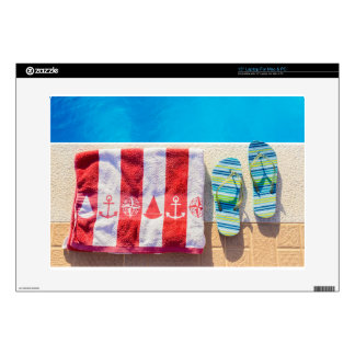 Bathing slippers and bath towel at swimming pool laptop skins