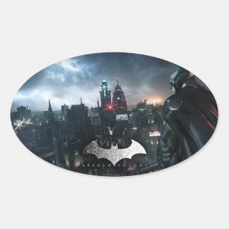 Batman que mira sobre ciudad pegatina ovalada