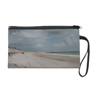 Beach and dune and jetty empty except one wristlet purse