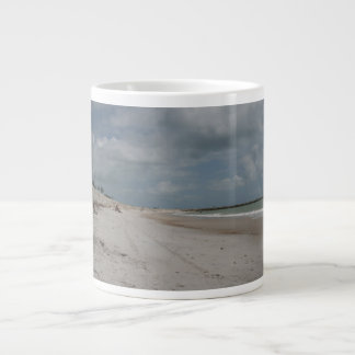 Beach and dune and jetty empty except one large coffee mug