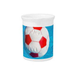 Beach ball floating  in blue swimming pool beverage pitcher