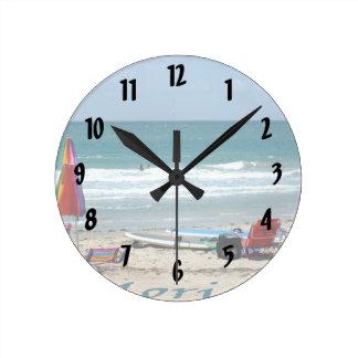beach chairs surfboards umbrellas sand ocean round wall clock