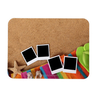 Beach scene with blank photo prints, towel, magnet