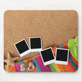 Beach scene with blank photo prints, towel, mouse pad