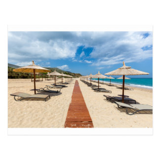 Beach umbrellas and loungers at greek sea postcard