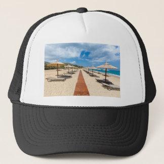 Beach umbrellas and loungers at greek sea trucker hat