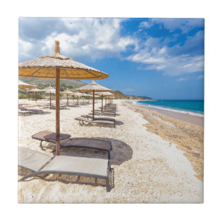 Beach umbrellas in rows on sandy beach with sea ceramic tile