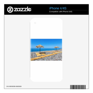 Beach umbrellas with path and stones at coast iPhone 4 skin