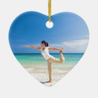beach yoga performed by a matured asian female Double-Sided heart ceramic christmas ornament