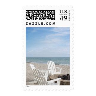 beachfront house with adirondack chairs and stamp