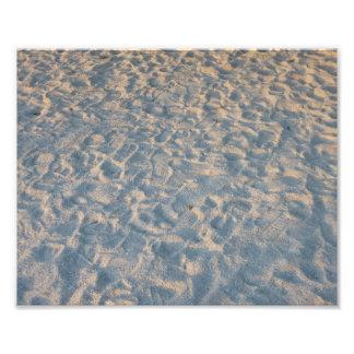 Beautful footprints all over beach sand, blue pink photo