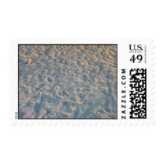 Beautful footprints all over beach sand, blue pink postage stamp