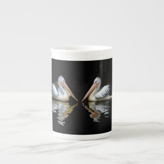 Beautiful pelicans reflection on black background tea cup