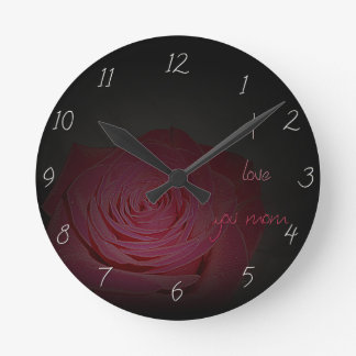 Beautiful pink rose on a black background round clock