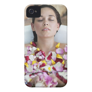 Beautiful young woman relaxing in bathtub with iPhone 4 cover