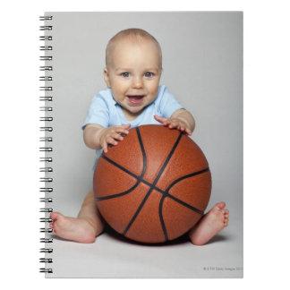 Bebé (6-9 meses) que lleva a cabo baloncesto, cuaderno