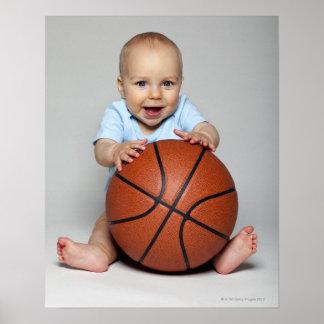 Bebé (6-9 meses) que lleva a cabo baloncesto, impresiones