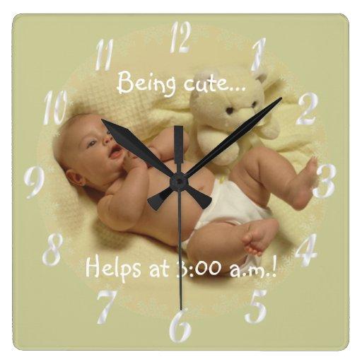 Bebé adorable que es ayudas lindas en el reloj de