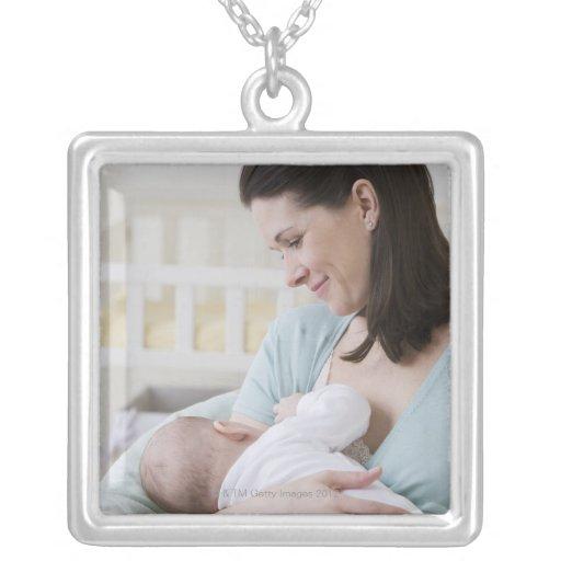 Bebé de amamantamiento de la madre grimpolas