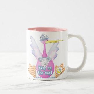 Bebé de la cigüeña en la manera taza de café de dos colores