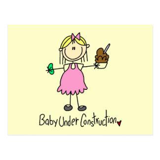 Bebé debajo de las camisetas y de los regalos de l tarjeta postal