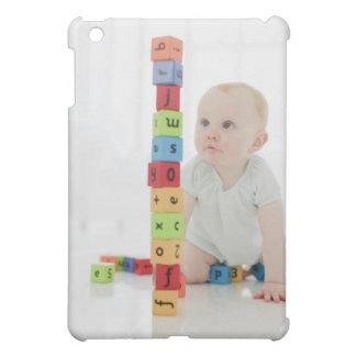 Bebé en el piso que mira bloques de madera apilado