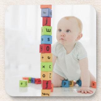 Bebé en el piso que mira bloques de madera posavasos de bebidas