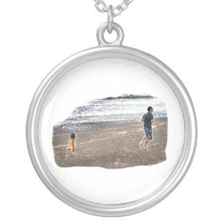 Bebé que persigue al hombre en arte de la playa colgante redondo