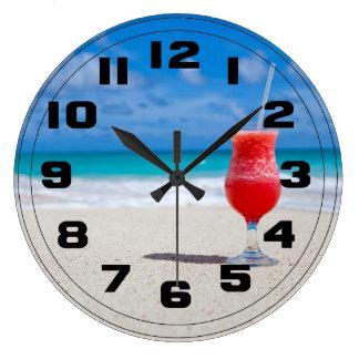 Bebida roja de la fresa en la playa de Sandy Relojes De Pared