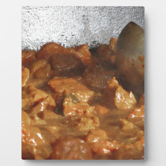 Beef goulash soup with metal serving spoon plaque