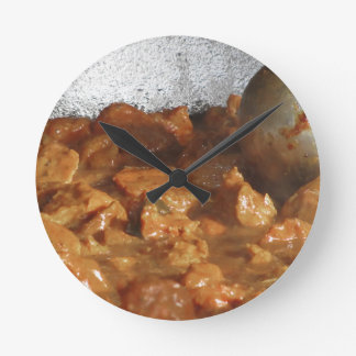 Beef goulash soup with metal serving spoon round clock