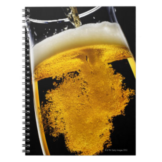 Beer been poured into glass notebook