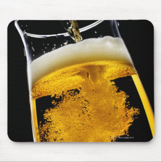 Beer been poured into glass, studio shot mouse pad